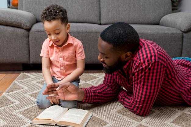 Libro de lectura negro del padre y del hijo en piso Foto gratis