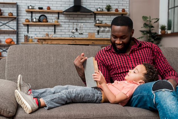 Libro de lectura negro del padre y del hijo en el sofá Foto gratis