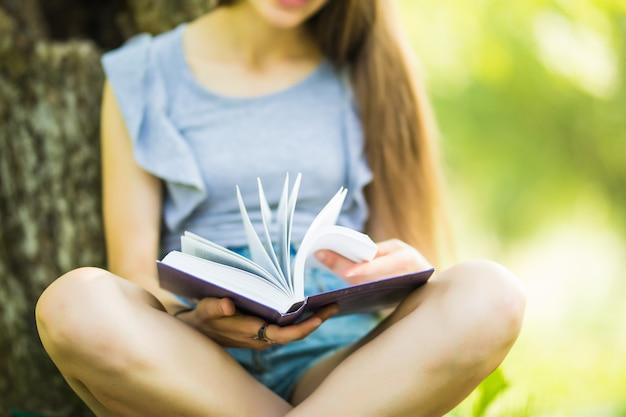 Libro de lectura de niña bonita en el parque. estudiante preparándose para el examen. ocio literario al aire libre. Foto gratis