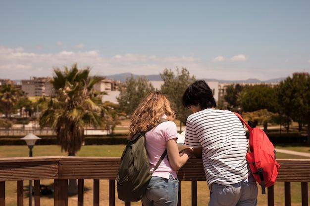 Libro de lectura de los pares cerca de la cerca de madera en el fondo de la ciudad Foto gratis