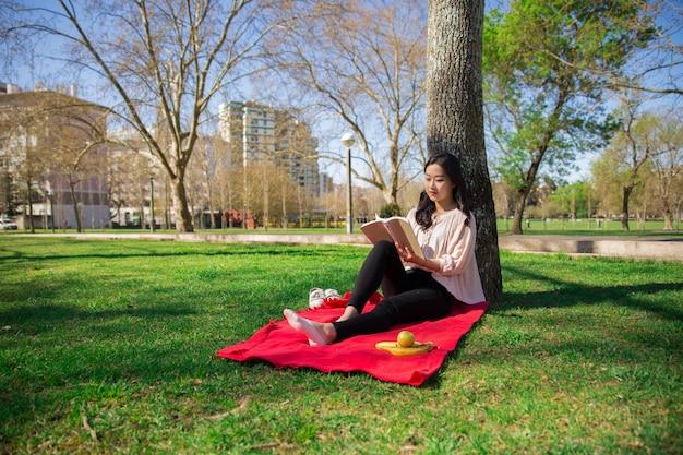 Libro de lectura pensativo serio de la muchacha del estudiante Foto gratis