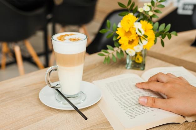 Libro de lectura de la persona cerca de la taza de café en el escritorio en la cafetería Foto gratis