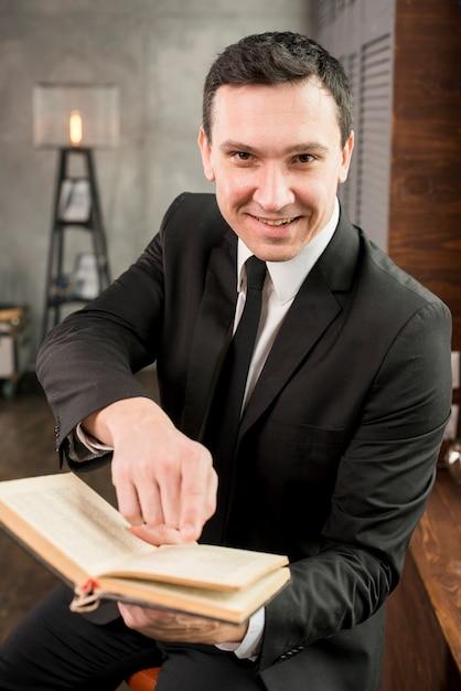 Libro de ofrecimiento del hombre de negocios contento joven sonriente Foto gratis