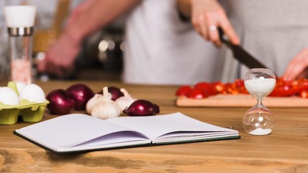 Libro de recetas y reloj de arena en la cocina. Foto gratis