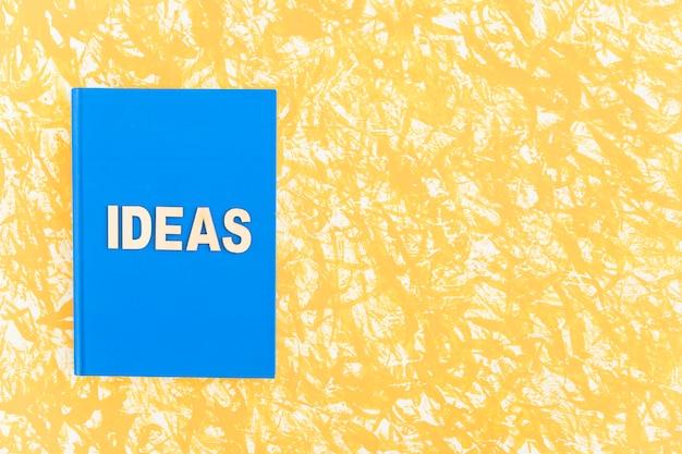 Libro de tapa azul ideas sobre fondo amarillo Foto gratis