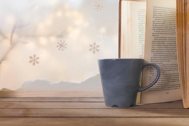 Libro y taza en mesa de madera cerca de banco de nieve, copos de nieve y luces de colores Foto gratis