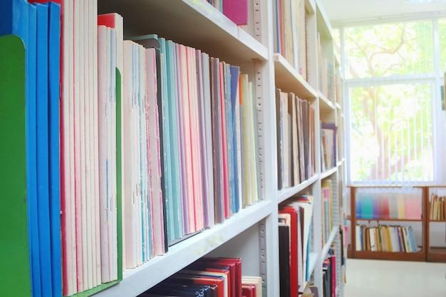 Los libros antiguos en estanterías con fondo borroso en la biblioteca pública. Foto Premium