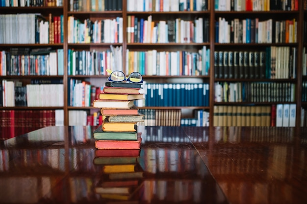 Libros antiguos y gafas en la biblioteca Foto gratis