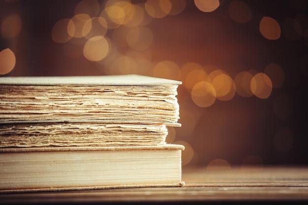 Libros antiguos en mesa de madera en el fondo de luces de