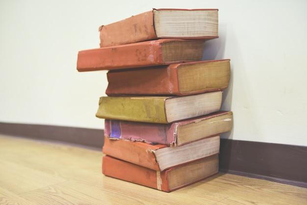 Libros antiguos en un piso de madera pila de libros en la sala de la biblioteca para negocios y educación Foto Premium