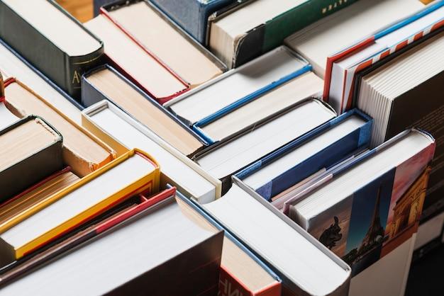 Libros apilados al azar en estante Foto gratis