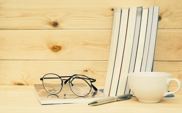 a1987f6737 Libros con gafas arriba. libro con gafas y taza de café en la mesa y fondo  de madera   Descargar Fotos premium