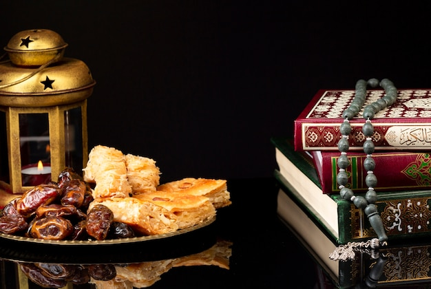 Libros islámicos con linterna y nastar. Foto gratis