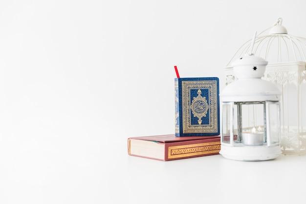 Libros islámicos y linterna Foto gratis