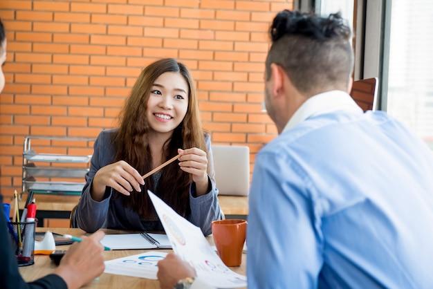 Líder empresarial femenina asiática escuchando a su personal en la reunión en Foto Premium