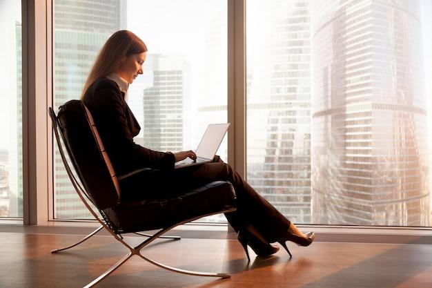 Líder femenino de la empresa trabajando en una computadora portátil en el hotel Foto gratis