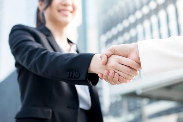 Líder de mujer de negocios joven haciendo apretón de manos con su pareja Foto Premium