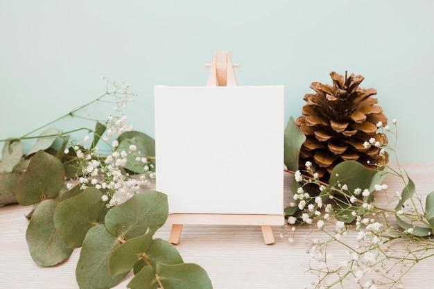 Lienzo en blanco sobre caballete en miniatura con hojas; flores de piña y aliento de bebé en escritorio de madera sobre fondo verde Foto gratis