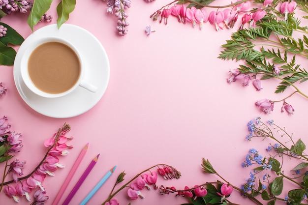 Lila púrpura y flores de corazón sangrante y una taza de café con cuaderno y lápices de colores en rosa pastel. Foto Premium