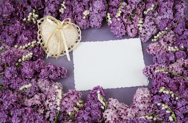 Las lilas y los lirios del valle están forrados con un marco, una hoja de papel en blanco y un corazón de encaje. Foto Premium