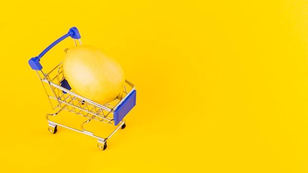 Limón dentro de la cesta de compras contra el fondo amarillo Foto gratis