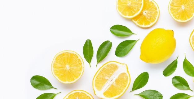 Limón fresco y rodajas con hojas aisladas en blanco Foto Premium