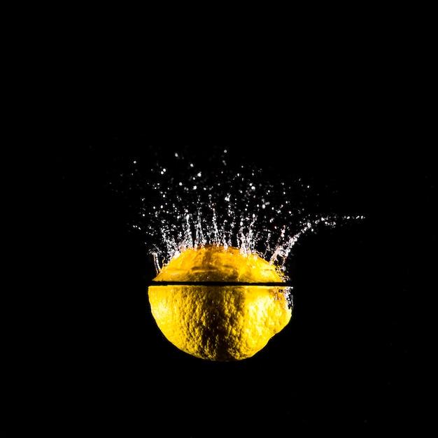 Limón sumergiéndose en el agua Foto gratis