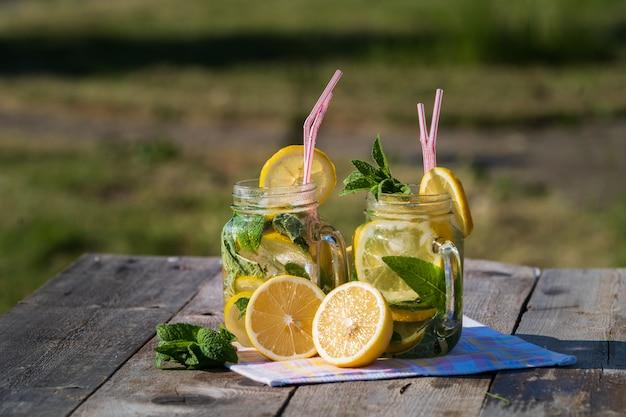 Limonada con limón, menta y hielo, en copas, sobre mesa de madera vieja, al aire libre. Foto Premium