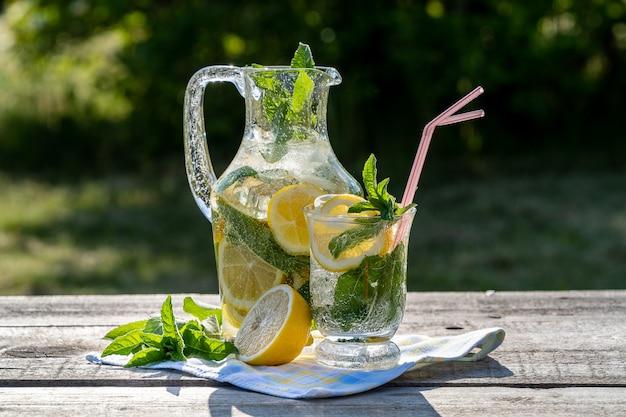 Limonada con limón, menta y hielo, en una jarra y un frasco, sobre una mesa de madera vieja, al aire libre. Foto Premium