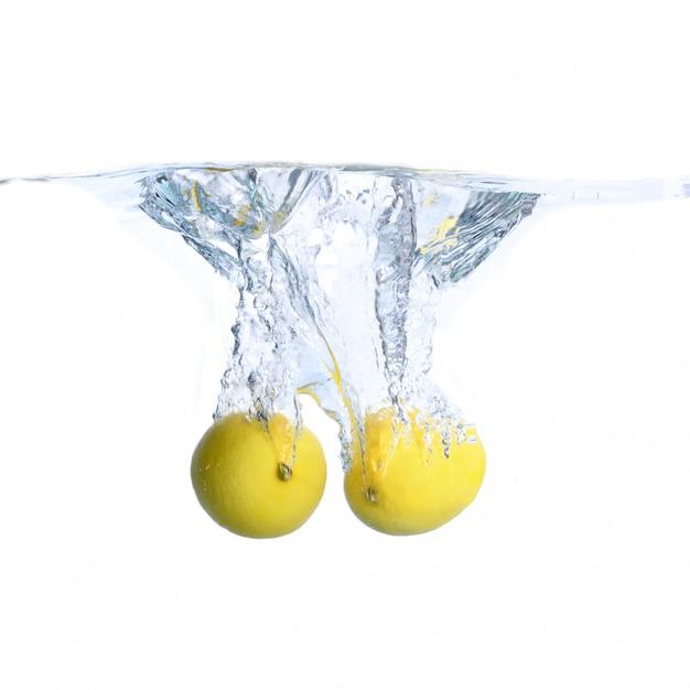 Limones en el agua con burbujas y salpicaduras. de cerca. aislado en blanco concepto e idea con limones Foto Premium