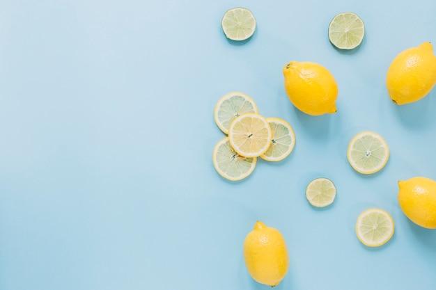 Limones enteros cerca de rodajas de cítricos Foto gratis