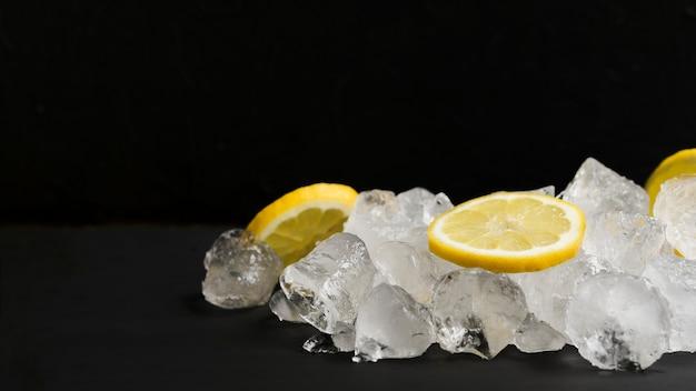 Limones y pila de cubitos de hielo. Foto gratis