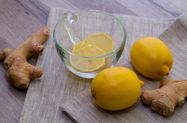 Limones y raíces de jengibre en gris como tratamiento contra la gripe estacional Foto Premium