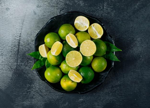 Limones verdes en un plato con rodajas vista superior sobre un fondo negro con textura Foto gratis
