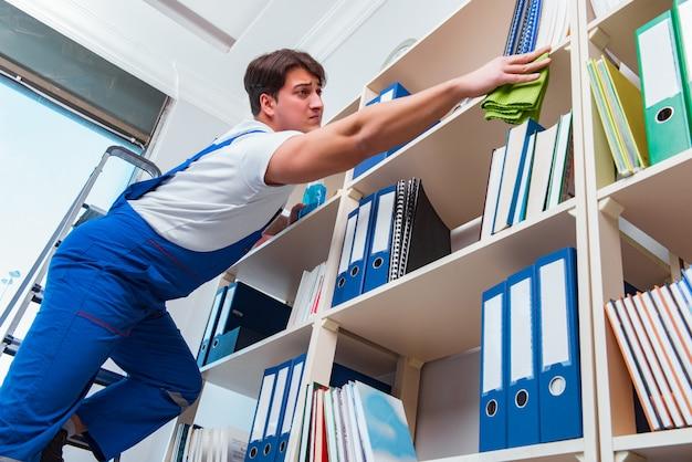 Limpiador de oficina masculino limpieza de estantes en la oficina Foto Premium