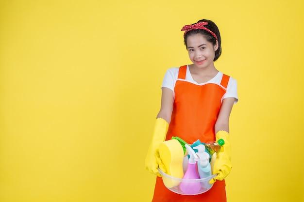 Limpieza una mujer hermosa con un dispositivo de limpieza en un amarillo. Foto gratis