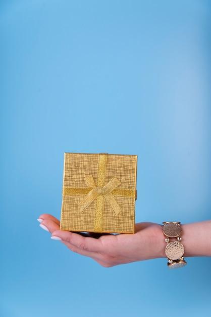 Linda caja de regalo en mano sobre fondo azul. Foto gratis