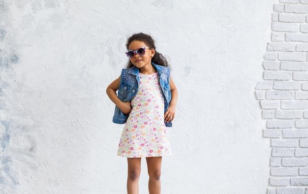 Linda chica afro contra la pared gris Foto Premium