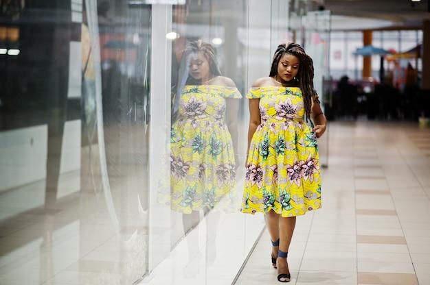 Linda chica afroamericana de pequeña altura con rastas, usar en el vestido amarillo de color, presentado en el escaparate de la tienda en el centro comercial. Foto Premium