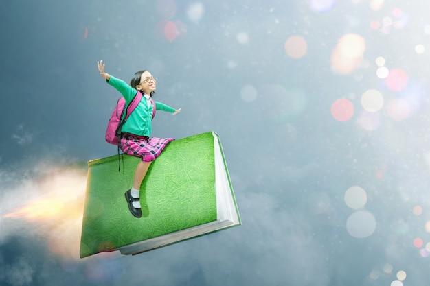 Linda chica asiática con gafas y mochila sentado en el libro Foto Premium