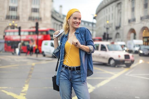 Linda chica bailando mientras escucha música, caminando en la calle Foto Premium