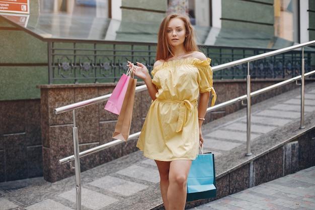 Linda chica con bolsa de compras en una ciudad Foto gratis