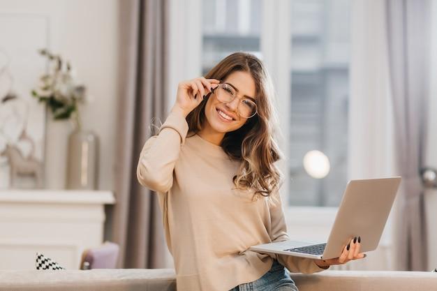 Linda chica en camisa beige tocando gafas y sosteniendo portátil con sonrisa Foto gratis