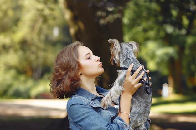 Linda chica en chaqueta azul jugando con perrito Foto gratis