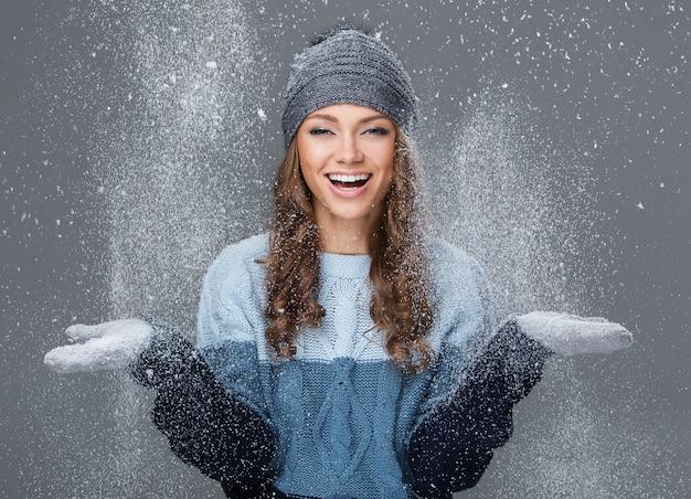 Linda chica con copos de nieve pasando un buen rato Foto gratis