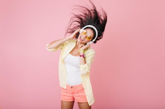 Linda chica hispana con piel bronceada con brazalete de moda y gafas naranjas escuchando música y bailando. foto interior de atractiva dama latina en chaqueta de algodón amarillo divirtiéndose. Foto gratis