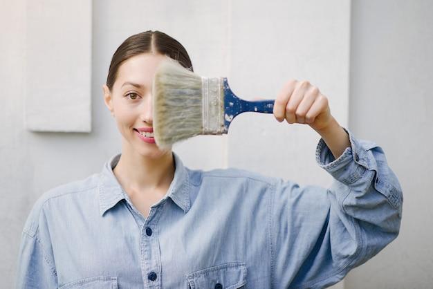 Linda chica de pie junto a la pared con herramientas de reparación Foto gratis