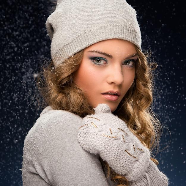 Linda chica rizada con guantes durante las nevadas Foto gratis