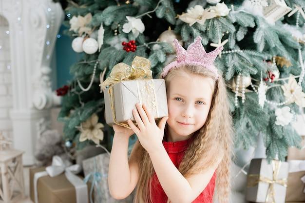 Linda chica rubia de 5 años con caja de regalo de navidad cerca del árbol de navidad. Foto Premium