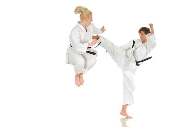 Linda chica rubia y un joven chico descarado de karate se dedican a la formación en un kimono sobre un fondo blanco. Foto Premium